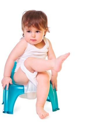 白高キー上に分離されて鍋の上に座っている小さな子供
