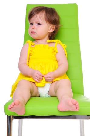 pie bebe: ni�a en un vestido amarillo se sienta en una silla verde centradas en el ni�o aislado en blanco estudio fotogr�fico