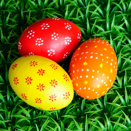 three colorful Easter eggs on grass photo