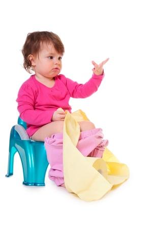 かわいい女の子は白で隔離されるペーパーのロールを保持している、ポットに座っています。