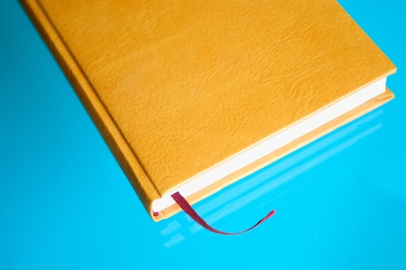 brown leather notebook with a red tab on the blue background. photo