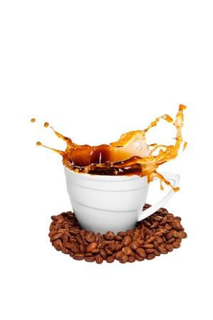 white cup with a splash of hot coffee. coffee beans scattered. isolated on a white background photo