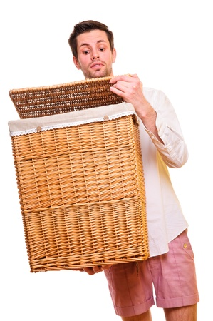 young man holding a large flasket in his hands. opens the lid and looks back. isolated on white photo