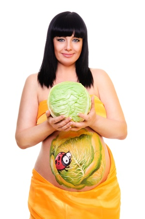 pregnant woman holding the cabbage in her hands. color picture on the abdomen. isolated on a white background photo