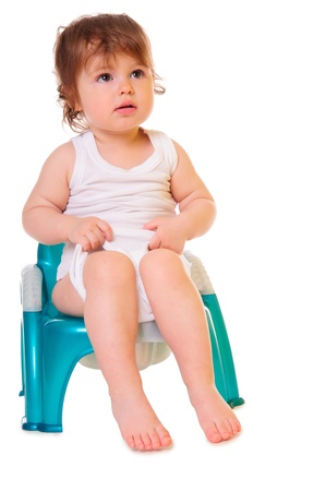 piddle: a small child sitting on the pot  isolated on white  high-key Stock Photo