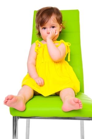 黄色のドレスの少女白いスタジオ写真上に分離されて子供に焦点を当てた緑椅子に座る