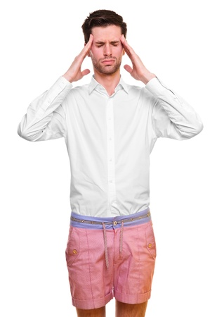 A young man grasping his head where the pain is - a killer headache or migraine  isolated on a white background  photo