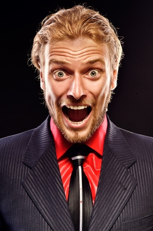 portrait of furious young man shouting on a black background photo
