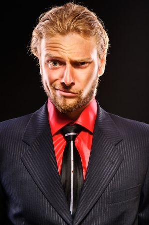 Portrait of young man with a doubting grimace on his face. close-up. isolated on a black background photo