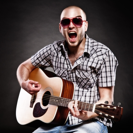 Portrait of a guitarist on a black background  a man shouts out loud and fun photo