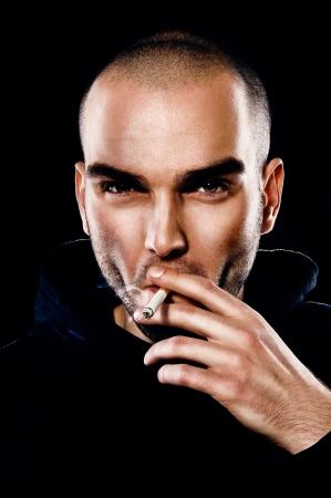 hombre calvo: Un retrato de un joven fumando un cigarrillo Foto de archivo
