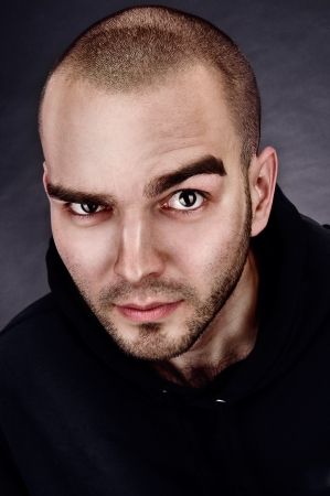 mid-frontal portrait of a man evil on grey background  Stock Photo