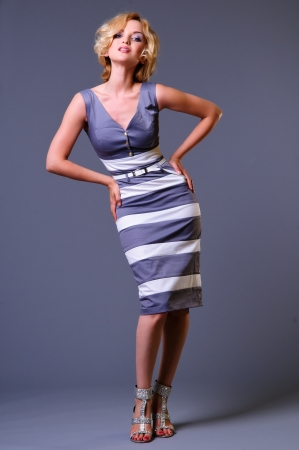 beautiful young businesswoman wearing a dress  in full growth  on a gray background Stock Photo - 14157185