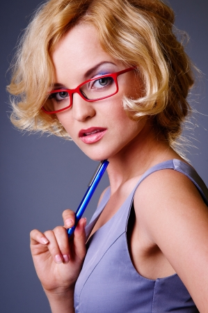 attractive businesswoman in red glasses, a pen in her hand  Close-up portrait on gray background Stock Photo - 14157190