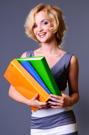 A beautiful smiling businesswoman is carrying colorful business folders photo