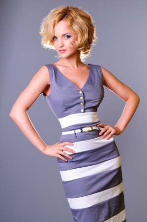 beautiful young businesswoman wearing a dress  standing  on a gray background photo