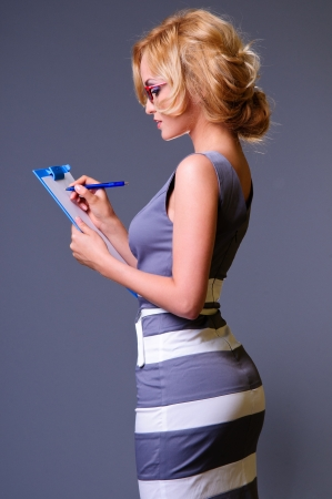 young happy sexy businesswoman in blue dress makes some notes in notepad photo