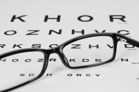 Reading eyeglasses and eye chart  close-up  on a light gray background