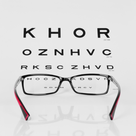 Reading Red and Black eyeglasses and eye chart  close-up  on a light gray background photo