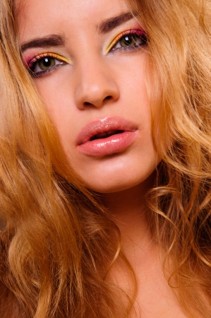 Beautiful woman with volume and shiny curly hair style, bright lips make-up  photo