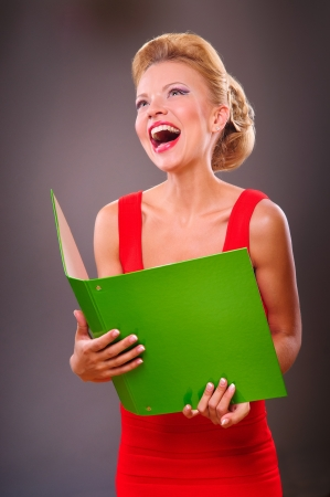 Portrait of a smiling blonde woman with the green folder in hands Stock Photo - 14588387