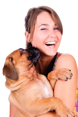 studio image of a young woman, with her bullmastiff dog, hugging it, both posing, looking happy and smiling
