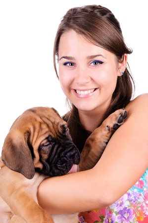 studio image of a young woman, with her bullmastiff dog, hugging it, both posing, looking happy and smiling photo