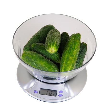 kitchen scales with cucumbers on white background Isolated photo