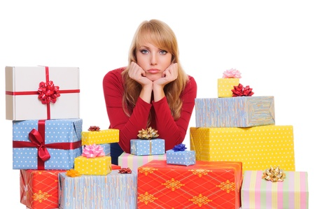 sad beautiful young woman and a pile of gift boxes  isolated on white background Stock Photo