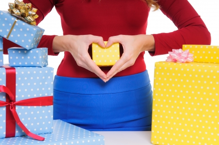 woman hands hold a gift box. fingers show a heart. Valentine day. closeup photo