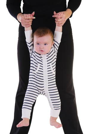mother holding a little child by the hand  baby hanging and makes developing exercises  isolated on white background Stock Photo - 16595817