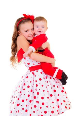 beautiful girl keep her little brother on hand  Hi dressed as Santa Claus  funny kids  brother and sister  portrait isolated on a white background
