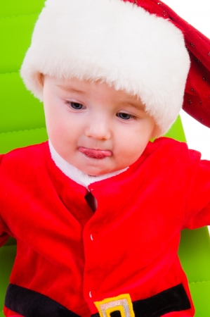 cute kid in Santa Claus clothes  sitting on a green chair photo