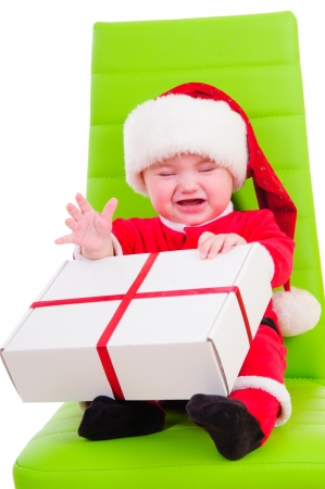 cute kid in Santa Claus clothes  sitting on a green chair and holding a big gift box photo