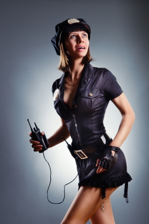 Fashion shoot of young sexy woman in clothes policeman with a radio in her hand photo