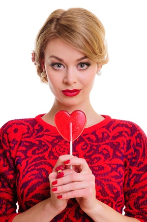 feast day: blonde woman holding a heart-shaped candy in her hands. feast day of St. Valentine. Portrait isolated on white background