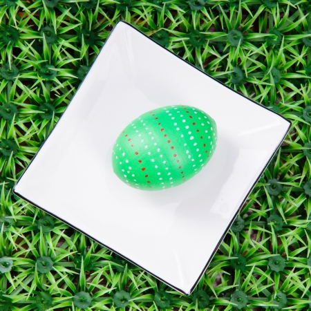 hand-drawn green Easter egg with plate on on artificial green grass photo