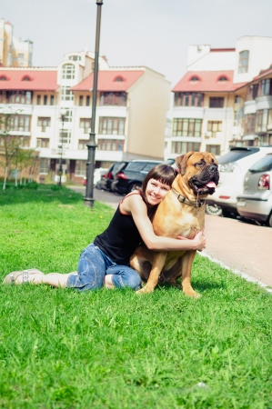 woman and dog bullmastiff sitting on green grass. girl hugging a puppy with love photo