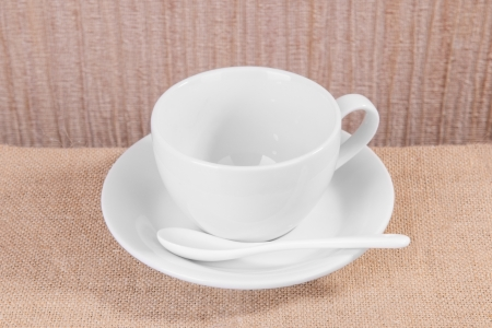 white porcelain cup and plate with a spoon on sacking photo