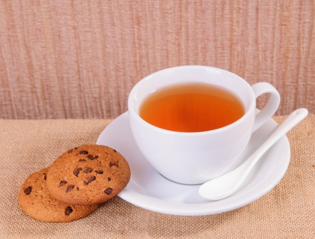 white cup of hot tea and cookies on sacking photo
