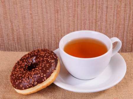 white cup of hot tea and chocolate donut on sacking photo