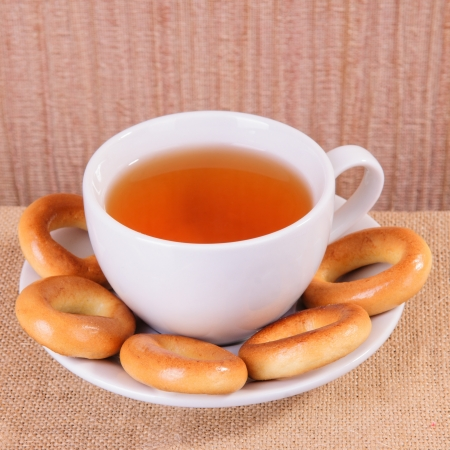 white cup of hot tea and bagels on sacking photo