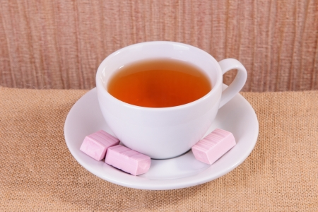 white cup of hot tea and candy on sacking photo