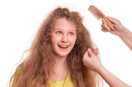 Beautiful smiling teenage girl. hairdresser hands keep the comb. isolated on white background photo