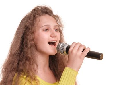 niño cantando: muchacha adolescente que canta con un micr?fono en la mano retrato aislado en fondo blanco