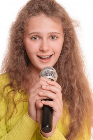 melodist: teen girl singing with a microphone in her hand  portrait isolated on white background Stock Photo