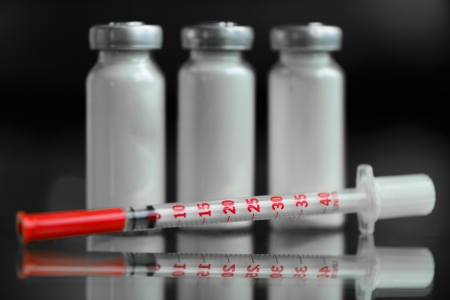 injectable: insulin syringe and  vials for injection, with white mortar  objects in macro mode