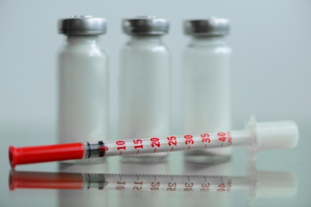 insulin syringe and  vials for injection, with white mortar. objects in macro mode Stock Photo