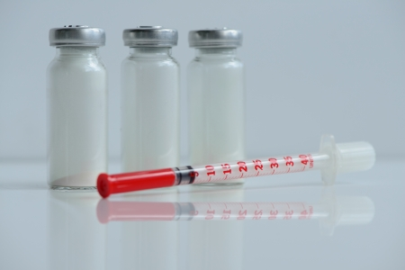 diabetes needles: insulin syringe and  vials for injection, with white mortar. objects in macro mode Stock Photo