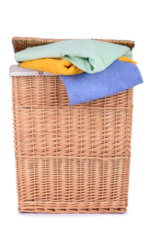 clothes basket with straw isolated on white background. towels in a basket